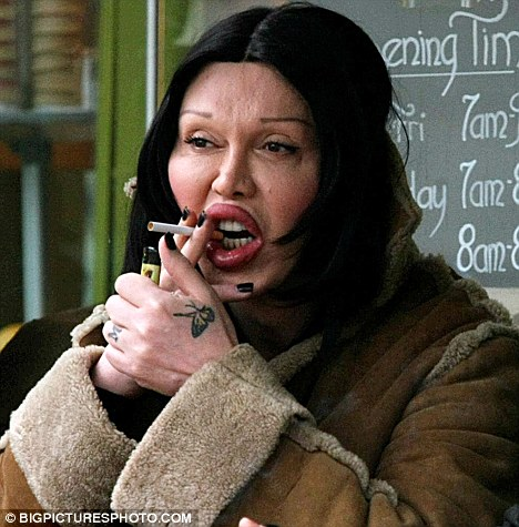 Pete Burns appears to struggle to clamp a cigarette